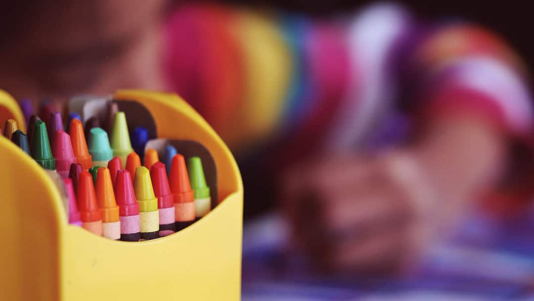 Child drawing with pack of crayons