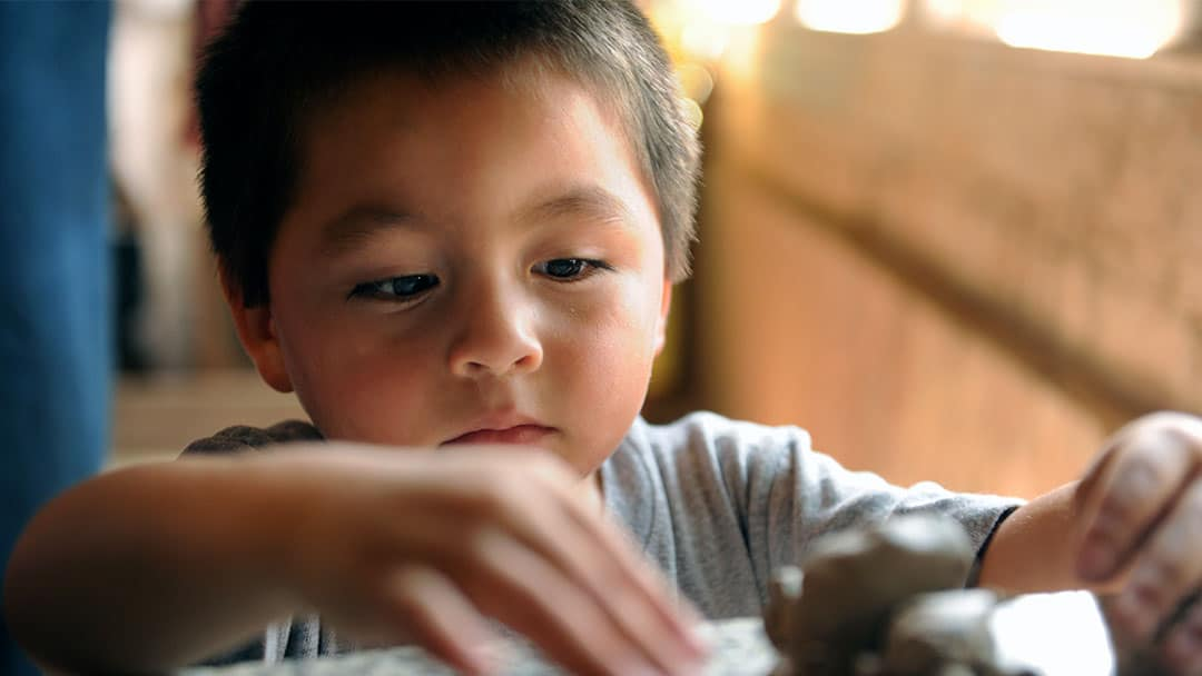Young boy making pottery