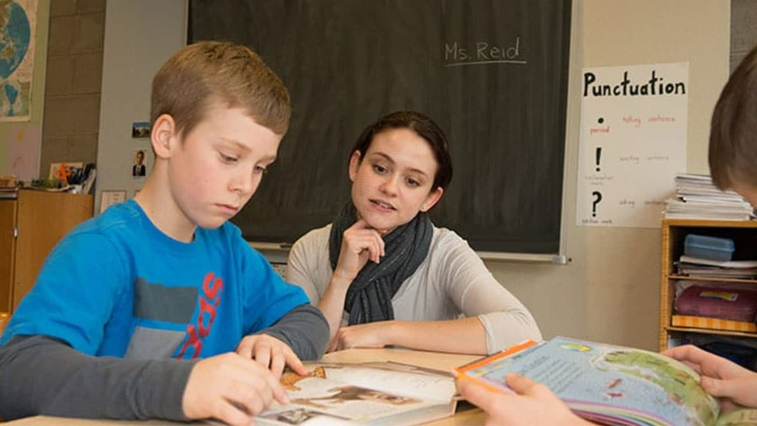 Teacher watching student completing work