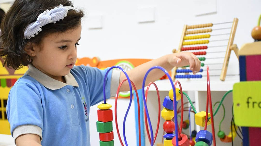 Preschool-aged girl playing with toy in classroom