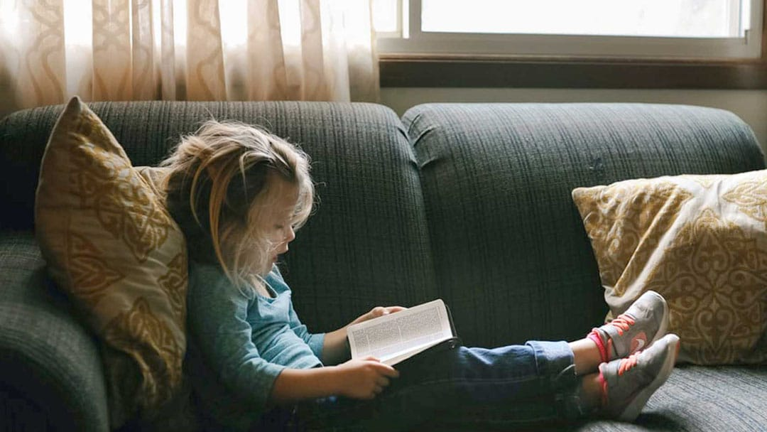 Young girl reading a book at home on a couch