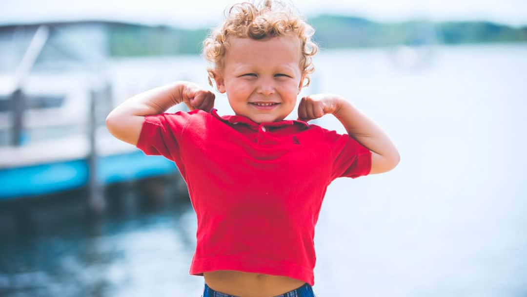 Boy near a boat dock in a red polo shirt flexing his muscles
