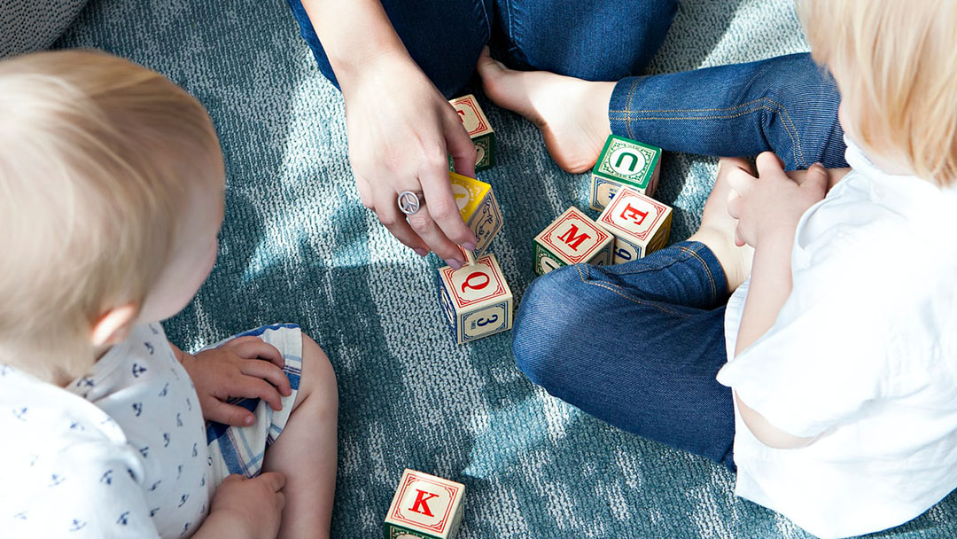 Kids and mother sitting in a circle playing with blocks