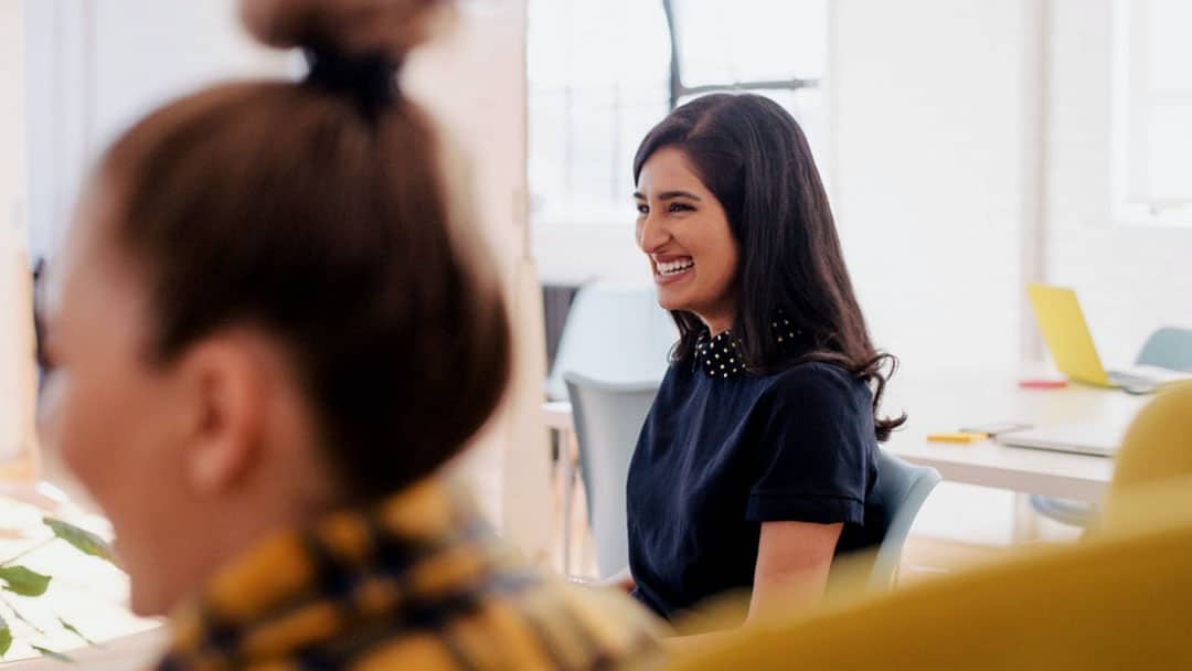 Young lady in navy blue blouse smiling with colleagues