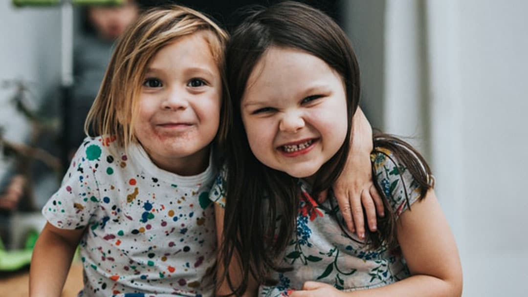 Two elementary school aged girls smiling together