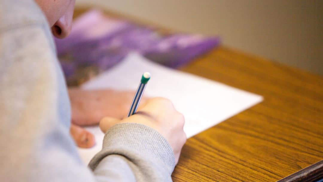 Person filling out a form with a pencil