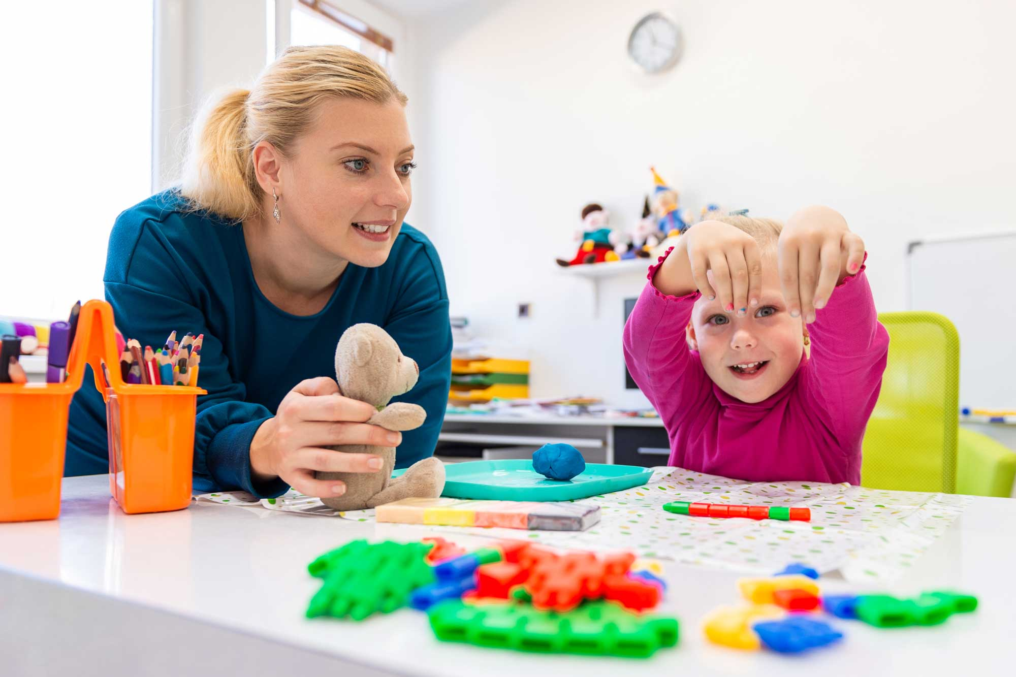 Teacher playing blocks with female student