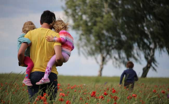 Dad carrying his kids in his arms through a field of flowers